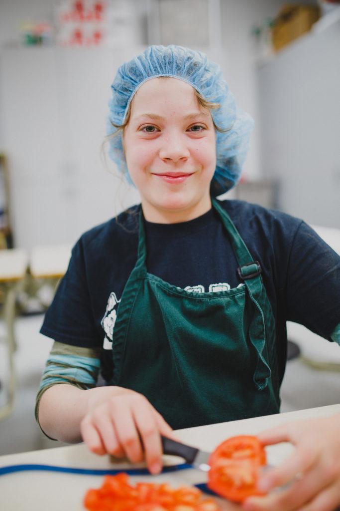 girl cutting tomato